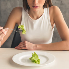 eating disorder awareness certification image of a woman holding lettuce with a fork